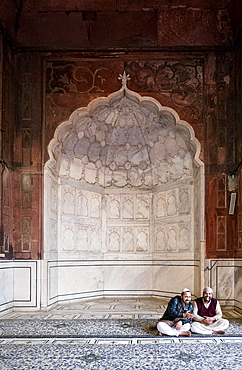 Men sitting by arch at Jama Masjid mosque in Delhi, India, Asia