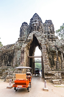 Tuk-tuks driving through the South Gate at Angkor Thom, Angkor, UNESCO World Heritage Site, Siem Reap Province, Cambodia, Indochina, Southeast Asia, Asia
