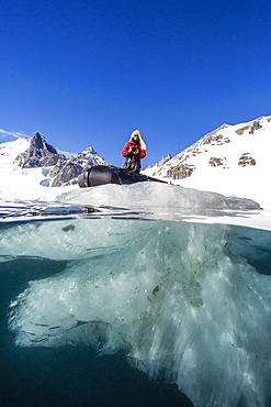 Above and below view of glacial ice and Zodiac in Orne Harbor, Antarctica, Polar Regions