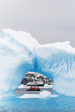 Lindblad Expeditions guests in a Zodiac as seen through an arch in an iceberg at Cierva Cove, Antarctica, Polar Regions