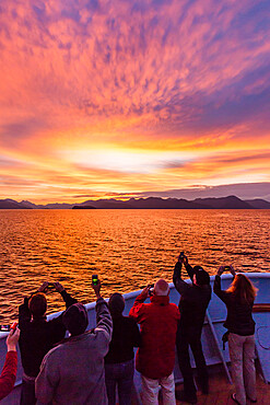 Lindblad/National Geographic guests enjoying sunset at Chichagof Island, southeast Alaska, USA.
