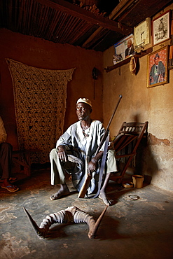 Man with hunting trophies and family pictures, Bante, Collines Department, Benin