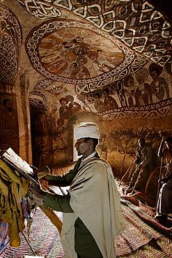Priest reading in an old goatskin manuscript, Abuna Yemata Guh church with mural painting, Hawzien, Tigray Region, Ethiopia