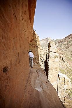 Man on a narrow path to monolithic church Abuna Yemata Guh, Hawzien, Tigray Region, Ethiopia