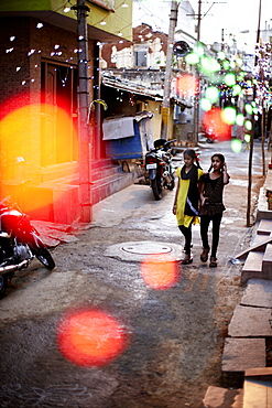 Girls walking along a street decorated with string of lights, Mysore, Karnataka, India