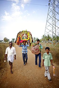 Men carrying deity statues and masks after a procession, Angadehalli Belur, Karnataka, India