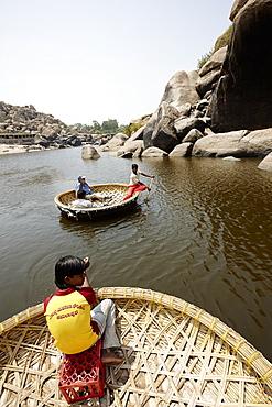 Boattrip in traditional round Coracle rowing boats, Tungabhadra River, Hampi, Karnataka, India