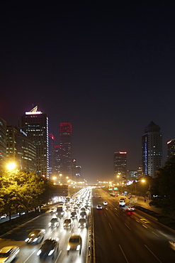 Night shot of urban traffic on ring road, skyscrapers in background, Guomao district, Beijing, China