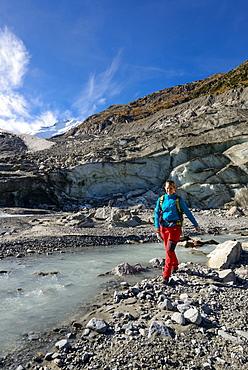 Woman crossing the Morteratsch Creek near the glacier mouth of Morteratsch glacier with view to Piz Bernina (4049 m), Engadin, G