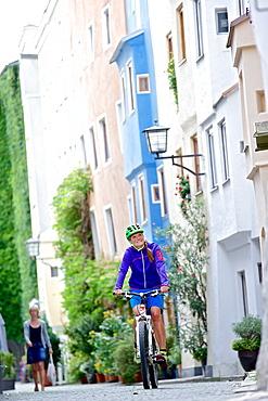 Female cyclist passing old town, Burghausen, Chiemgau, Bavaria, Germany