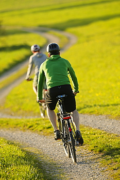 Two cyclists riding e-bikes, Munsing, Upper Bavaria, Germany