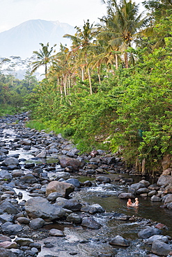 Father and son taking a bath in a river, riverbed, rocks, stones, local Balinese taking baths here, trees, local custom, intercu