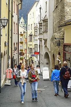 Persons walking along alley Langer Graben in old town, Hall, Tyrol, Austria