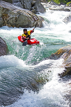 Kayaker on the crystal clear waters of the Verzasca, Ticino, Switzerland