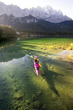 Kayaker paddling on the Eibsee below Zuspitze, Grainau, Bavaria, Germany