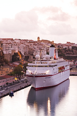 Cruise ship MS Deutschland (Reederei Peter Deilmann) at pier and old town buildings at sunset, Mahon, Menorca, Balearic Islands,