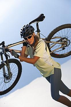 Young woman carrying mountain bike on her shoulder, Monte Baldo, Lake Garda, Italy