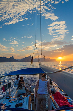 A young man sitting at the steering wheel, steering a sailing yacht at sunset, Mallorca, Balearic Islands, Spain, Europe