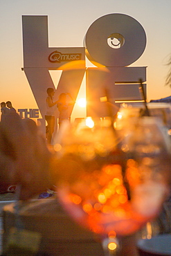 Love sculpture on the beach seen through a cocktail glass at sunset, Ostend, Flanders, Flemish Region, Belgium