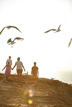 Young family walking along the steep coast, Rota Vicentina, Portugal