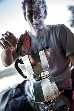 Young man making coffee with a camp cooker, Freilassing, Bavaria, Germany