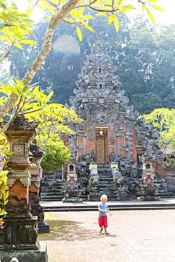 Boy in front of temple Pura Durga Kutri, Kutri, Ubud, Bali, Indonesia