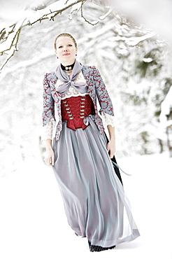Young woman wearing a Dirndl standing in snowy scenery, Irsee, Bavaria, Germany