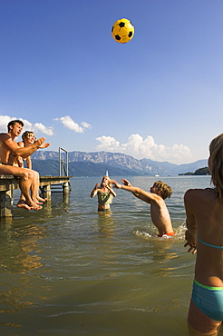 Family at lake Attersee, children standing in water playing with a ball, Salzkammergut, Upper Austria, Austria