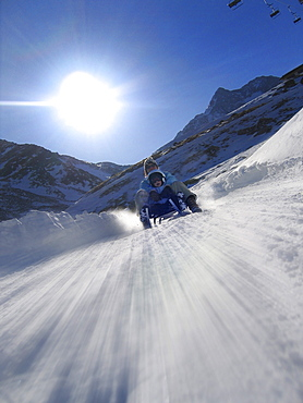 Mother and son on sledge, Lazaun run, Schnals Valley, South Tyrol, Italy, MR