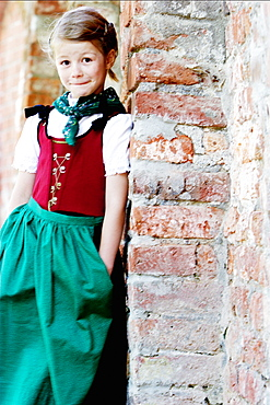 Girl wearing dirndl dresses leaning against wall, Irsee, Bavaria, Germany