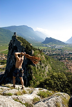 Climber on summit throwing a rope, Arco, Trentino-Alto Adige/Südtirol, Italy