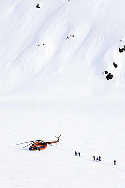 Group of skiers near a helicopter, Heliskiing, Kamchatka Peninsula, Sibiria, Russia