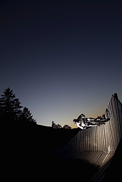 Mountain biker passing wallride, Oberammergau, Bavaria, Germany