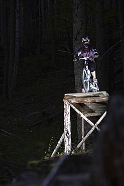 Mountain biker standing on ramp, Oberammergau, Bavaria, Germany