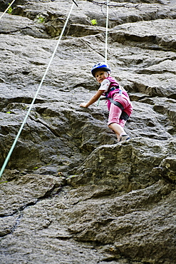 Girl (8-9 years) climbing on a rock, Upper Bavaria, Bavaria, Germany