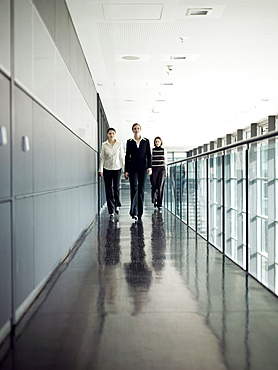 Three businesswomen walking along corridor, Munich, Bavaria, Germany