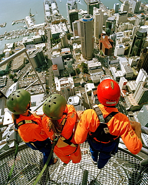 Three people on top of Sky Tower looking over Central Business District and Waitemata Harbour, Auckland, North Island, New Zealand