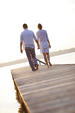 Couple walking hand in hand along jetty, Ambach, Lake Starnberg, Bavaria, Germany