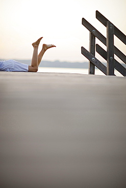 Woman lying on jetty at lake Starnberg, Ambach, Bavaria, Germany