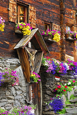 Crucifix and flower decoration at mountain farmhouse, valley Pfossental, Texel range, Oetztal range, South Tyrol, Italy