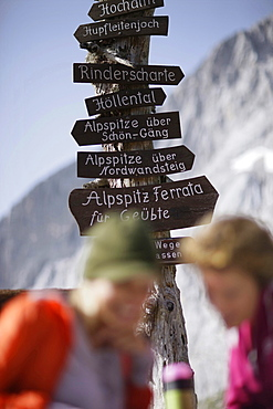 Two young women near sign post, Werdenfelser Land, Bavaria, Germany