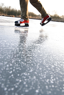 Man skating on lake Ammersee, Upper Bavaria, Germany