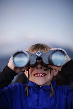 Boy (7 years) looking through binoculars, Brixen, Tyrol, Austria