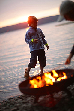 Boy near campfire at Lake Starnberg, Bavaria, Germany