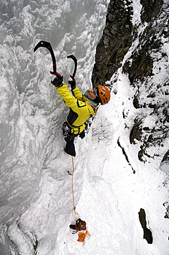 Young woman ice climbing, Engadin, Grissons, Switzerland, Europa