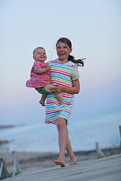 Girl carrying baby on jetty, Formentera, Balearic Islands, Spain