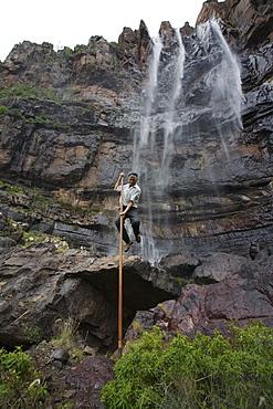 Man jumping with canarian crook in front of waterfall Cascada el Escobar, El Risco valley, Parque Natural de Tamadaba, Gran Canaria, Canary Islands, Spain, Europe