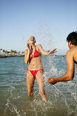 Young couple splashing each other in sea