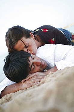 Couple in clothes lying on beach, woman kissing man' s neck
