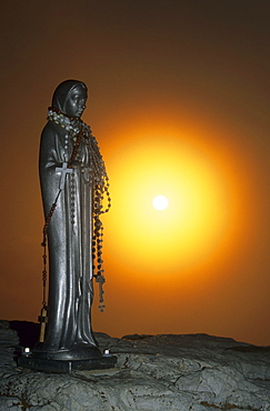 Madonna with rosary and the rising sun as backlight, Piz Boe, Sella Mountains, Dolomites, South Tyrol, Italy